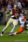 FSU quarterback Jameis Winston rushes downfield as Florida Gators defensive lineman Dante Fowler, Jr. tries to bring him down.  Florida Gators vs FSU Seminoles.  November 22th, 2014. Gator Country photo by David Bowie.