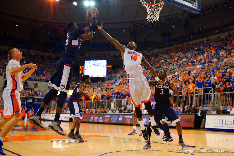 Florida Gators forward Dorian Finney-Smith battles for a rebound against UCONN Huskies center Amida Brimah during the second half.  Florida Gators vs UCONN Huskies.  January 3rd, 2015. Gator Country photo by David Bowie.