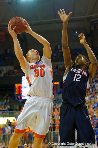 Florida Gators forward Jacob Kurtz leaps toward the net being guarded by UCONN Huskies forward Kentan Facey.  Florida Gators vs UCONN Huskies.  January 3rd, 2015. Gator Country photo by David Bowie.