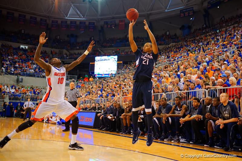 Florida Gators center Jon Horford launches a three pointer over the head off Florida Gators forward Dorian Finney-Smith during the second half.  Florida Gators vs UCONN Huskies.  January 3rd, 2015. Gator Country photo by David Bowie.