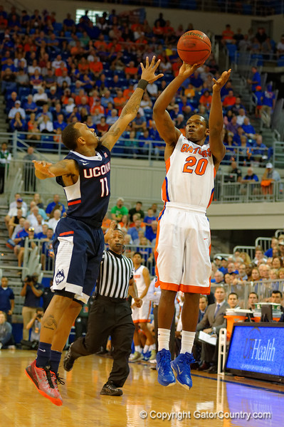 Florida Gators guard Michael Frazier II puts up a shot over the outstretched arm of UCONN Huskies guard Ryan Boatright in the first half.  Florida Gators vs UCONN Huskies.  January 3rd, 2015. Gator Country photo by David Bowie.