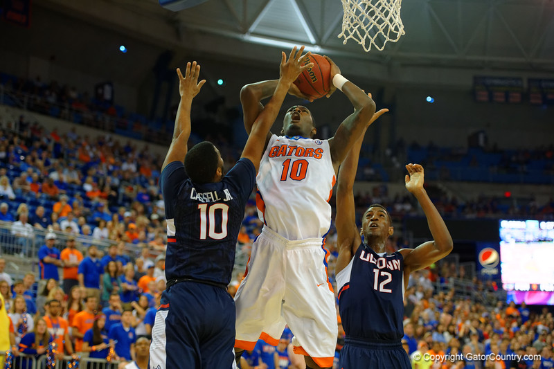 Florida Gators forward Dorian Finney-Smith leaps up for a shot in the first half, being guarded by UCONN guard Sam Cassell Jr. and UCONN forward Kentan Facey.  Florida Gators vs UCONN Huskies.  January 3rd, 2015. Gator Country photo by David Bowie.