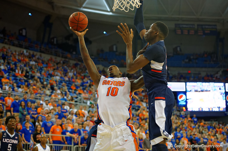 Florida Gators forward Dorian Finney-Smith with a shot attempt in the first half while being guarded by UCONN center Amida Brimah.  Florida Gators vs UCONN Huskies.  January 3rd, 2015. Gator Country photo by David Bowie.