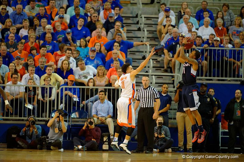 UCONN Huskies guard Ryan Boatright makes a three point basket over Florida Gators guard Chris Chiozza during the first half.  Florida Gators vs UCONN Huskies.  January 3rd, 2015. Gator Country photo by David Bowie.