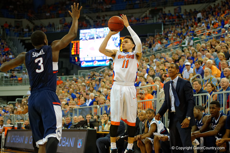 UCONN Huskies head coach Kevin Ollie watches on as Florida Gators guard Chris Chiozza drains a three pointer in the first half.  Florida Gators vs UCONN Huskies.  January 3rd, 2015. Gator Country photo by David Bowie.