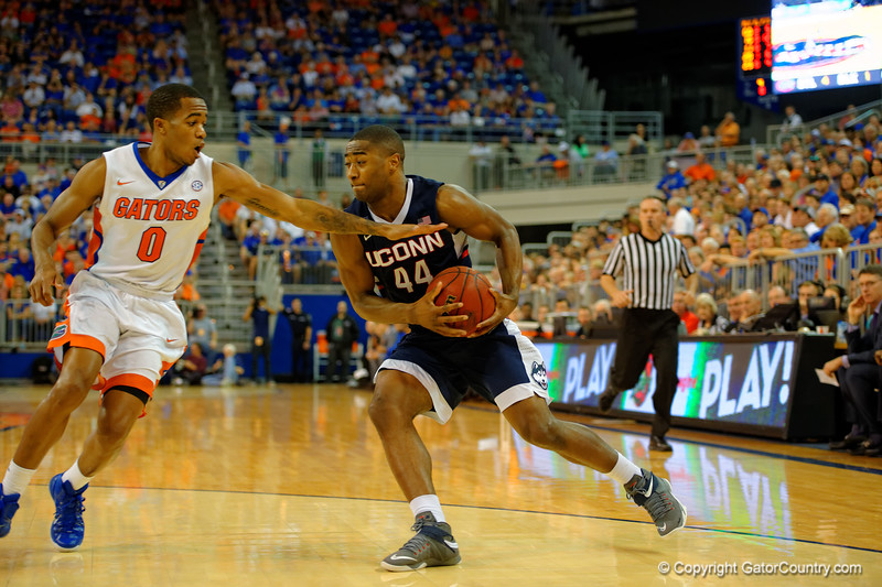 UCONN Huskies guard Rodney Purvis dribbles toward the basket while Florida Gators guard Kasey Hill defends.  Florida Gators vs UCONN Huskies.  January 3rd, 2015. Gator Country photo by David Bowie.