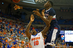UCONN center Amida Brimah blocks a shot by Florida Gators forward Dorian Finney-Smith in the first half.  Florida Gators vs UCONN Huskies.  January 3rd, 2015. Gator Country photo by David Bowie.