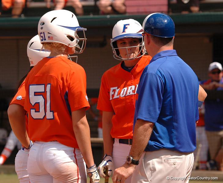 With base runners Sami Fagan and Katie Medina, Coach Walton talks with Kelsey Horton about her at bat