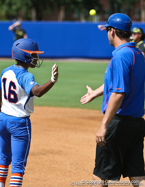 Florida junior center fielder Michelle Moultrie slaps hands with volunteer coach Coy Adkins during the Gator's 9-1 victory against the Oregon Ducks in the first day of the NCAA Super Regionals  on Friday, May 27, 2011 at Katie Seashole Pressly Stadium in Gainesville, Fla. / photo by Rob Foldy