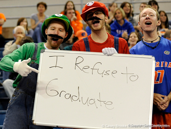 """Florida fans dressed as popular video game characters Mario and Luigi from Super Mario Brother hold a sign, which reads """"I refuse to graduate."""" The Gators clinched their last home game with a 3-0 win over the Crimson Tide at the O'Connell Center on Saturday, November 23, 2008. (Casey Brooke Lawson / Gator Country)"""
