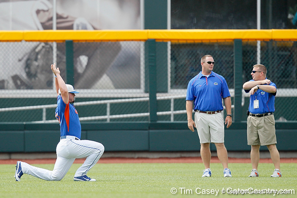 Florida sophomore Austin Maddox stretches as strength coach Paul Chandler and athletic trainer John Barrett look on during the Men's College World Series practice day on Friday, June 17, 2011 at TD Ameritrade Park in Omaha, Neb. / Gator Country photo by Tim Casey