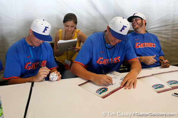 Florida freshman Keenan Kish speaks with a reporter while sophomore Brian Johnson and freshman pitcher Daniel Gibson sign autographs during the Men's College World Series practice day on Friday, June 17, 2011 at TD Ameritrade Park in Omaha, Neb. / Gator Country photo by Tim Casey