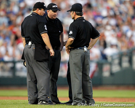 Umpires conference during the Gators' 8-4 win against the Texas Longhorns in the College World Series on Saturday, June 18, 2011 at TD Ameritrade Park in Omaha, Neb. / Gator Country photo by Tim Casey