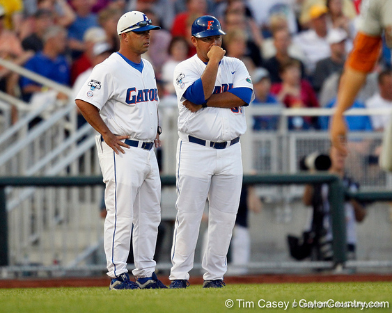 Florida head coach Kevin O'Sullivan talks with baseball assistant coach Craig Bell during the Gators' 8-4 win against the Texas Longhorns in the College World Series on Saturday, June 18, 2011 at TD Ameritrade Park in Omaha, Neb. / Gator Country photo by Tim Casey