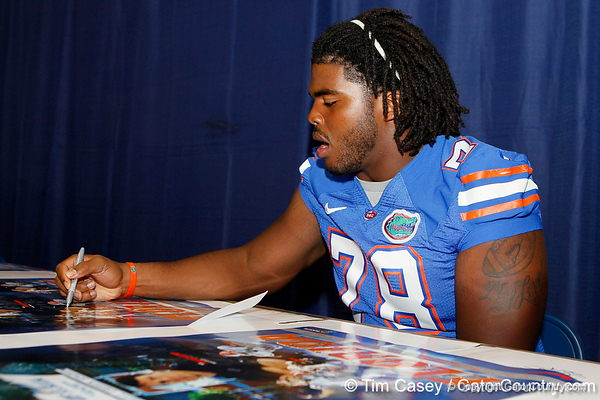Florida redshirt junior guard David Young signs an autograph during the Gators' annual Fan Day event on Saturday, August 20, 2011 at the Stephen C. O'Connell Center in Gainesville, Fla. / Gator Country photo by Tim Casey