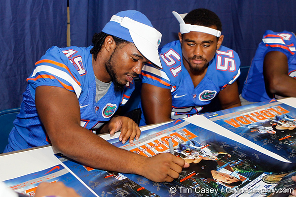Florida sophomore linebacker Darrin Kitchens and redshirt freshman linebacker Michael Taylor sign autographs during the Gators' annual Fan Day event on Saturday, August 20, 2011 at the Stephen C. O'Connell Center in Gainesville, Fla. / Gator Country photo by Tim Casey