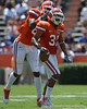 UF defensive end Lynden Trail congratulates cornerback Cody Riggs (31) after Riggs made a diving interception in the 2011 Orange and Blue Debut at Ben Hill Griffin Stadium on Saturday, April 9, 2011. / Gator Country photo by Harrison Diamond