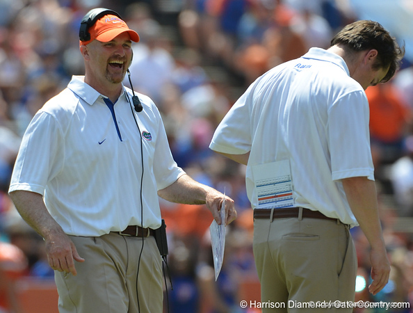 UF defensive coordinator Dan Quinn, left, laughs while talking with head coach Will Muschamp on the field during the 2011 Orange and Blue Debut at Ben Hill Griffin Stadium on Saturday, April 9, 2011. / Gator Country photo by Harrison Diamond