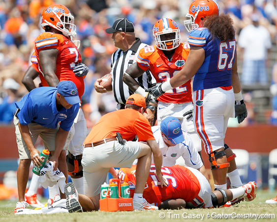 Florida sophomore defensive tackle Sharrif Floyd and sophomore safety Matt Elam check on sophomore defensive tackle Dominique Easley during the Gators' spring football game on Saturday, April 9, 2011 at Ben Hill Griffin Stadium in Gainesville, Fla. / Gator Country photo by Tim Casey