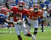 UF linebacker Gideon Ajagbe (25) sprints towards quarterback Tyler Murphy as he hands off to Malcolm Jones during the 2011 Orange and Blue Debut at Ben Hill Griffin Stadium on Saturday, April 9, 2011. / Gator Country photo by Harrison Diamond