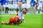 WR Quinton Dunbar is tackled after making his catch.  Gators vs Miami.  9-07-13.