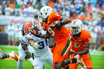 DB Cody RIggs tries to tackle RB Duke Johnson.  Gators vs Miami.  9-07-13.