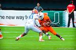 Miami RB Duke Johnson tries to elude LB Michael Taylor.  Gators vs Miami.  9-07-13.