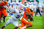 LB Antonio Morrison tries to tackle Miami WR Herb Waters.  Gators vs Miami.  9-07-13.