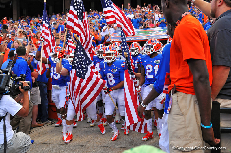 The Florida Gators bearing American flags to salute those who serve take the field for the Georgia Southern game.  Florida Gators vs Georgia Southern Eagles.  Gainesville, FL.  November 23, 2013.