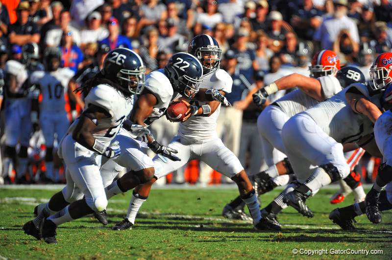 Georgia Southern QB Kevin Ellison looks whether to hand the ball off to FB Irving Huggins or keep it himself in their triple option attack.  Florida Gators vs Georgia Southern Eagles.  Gainesville, FL.  November 23, 2013.