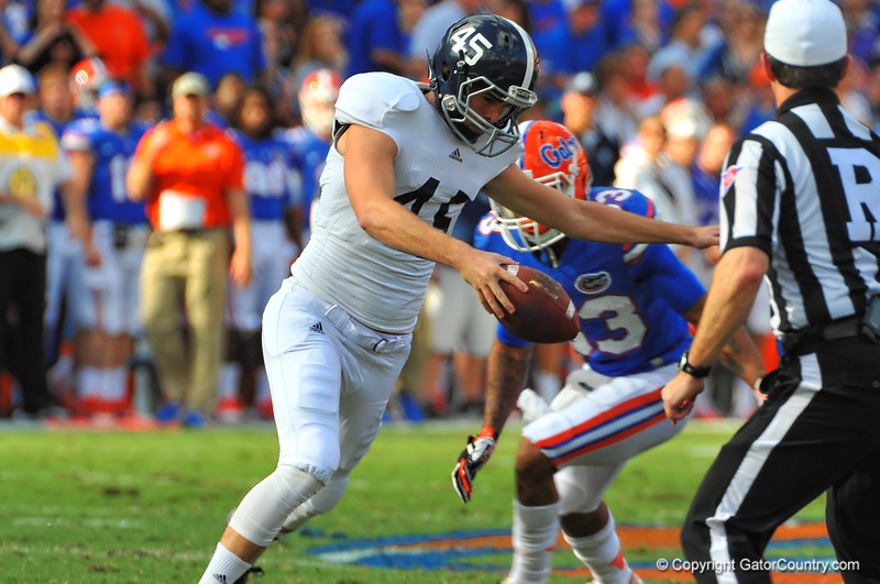 Georgia Southern punter Luke Cherry rushes to get the punt off after a mishandled snap before Florida Gator Solomon Patton gets to him.  Florida Gators vs Georgia Southern Eagles.  Gainesville, FL.  November 23, 2013.