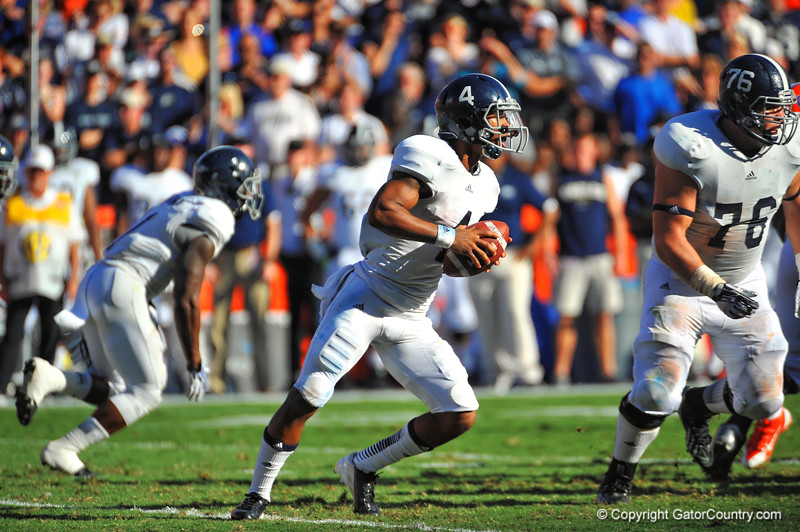 Georgia Southern QB Kevin Ellison drops back and looks downfield before tucking the ball and running upfield.  Florida Gators vs Georgia Southern Eagles.  Gainesville, FL.  November 23, 2013.