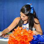 A Gator cheerleader signs a poster for a fan at the Gator Fan Day.  Stephen C. O'Connell Center.  August 17th, 2013