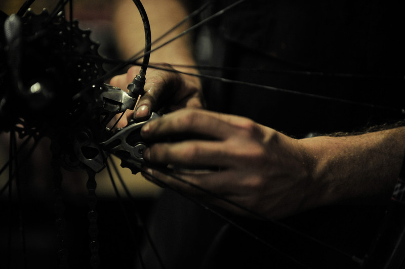 """Steven Morris, owner of Mello Velo Bicycle Shop, repairs a gear shifter on an old bicycle, Sept. 26. Morris opened his Syracuse, N.Y., shop in November 2009. <br /> """"You have to make your customers happy,"""" Morris said. """"Sometimes you have to get your hands dirty to keep up.""""  Photo by Matthew Freire 