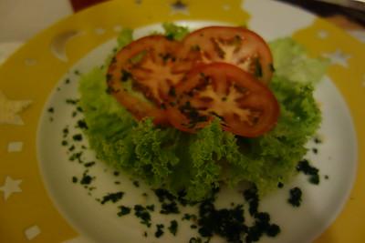 Salat und 3 dünn geschnittene Tomatenscheiben auf das unter Brötchen legen