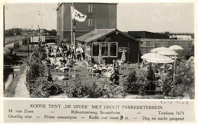 G0022 <br /> Rijksstraatweg 61, koffietent De Uiver van M. van Zoen, sinds 1933 bestaande uit deze tweedehands legerkantine. In 1938 kwam er een tweede barak bij; toen werd er ook een groot parkeerterrein aangelegd. Later is de koffietent afgebroken voor een groter pand. Op de achtergrond de bollenschuur van W. Eldering.