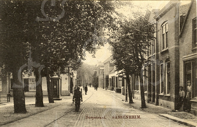 G0426 <br /> Gezicht op de Hoofdstraat vanaf de Klapbrug. De brug werd zo genoemd omdat de houten brugdelen rammelden als er verkeer overheen ging. Links de Oude Haven met de sokkel van de telegraafmast. (Nabij de Oude Postbrug stond ook zo'n mast.) Geheel rechts het huis van de fam. Noordermeer, dan met de twee voordeuren naast elkaar de panden van (later) de dames Van Nieuwkoop  en J. van Nieuwkoop. Daar weer achter het pand waar nu keurslager Scholten is; op deze foto is het nog een woonhuis. Zie ook foto An0336. <br /> Het vooruitstekende witte pand is de voormalige school met zusterhuis. Op de achtergrond de donkere serre van hotel café-restaurant 't Bruine Paard. Foto: 1912.