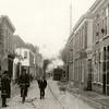 G0415 <br /> Links het pand van J.v.d. Meer, daarna de korenmaalderij, later wijnhandel. Dan volgt boekhandel J.W. de Gruijter en het witte huis, dat tot 1899 als zusterhuis en school gebruikt werd. Later kwam bakker Hooijmans in het pand. Rechts een deel van het woonhuis van Bruijnen. Via de poort was de smederij te bereiken. Het volgende pand was jarenlang de winkel van C. Jamin. Daarna het huis van T. Vos, de kolenhandel. De stoomtram Bello is in aantocht! Foto: 1911.