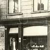 G0457 <br /> Van Lierop voor zijn winkel in fijne vleeswaren, kaas, boter etc. aan de Hoofdstraat. Hij liep met een verhoogde rechterschoen en bracht met een transportfiets (de mand voorop) de bestellingen rond. Later werd het de groentewinkel van Nederstigt en daarna het Sassenheims Vloerenhuis. Let op de reclamebordjes aan de muur.