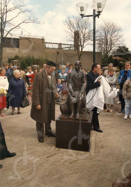 G1781 <br /> De onthulling door burgemeester Kret van het kunstwerk bij de St. Pancratiuskerk. Het bronzen beeld met de naam 'De tuinder' is gemaakt door G. Prins uit Giessenburg. De man met alpinopet die bij het beeld staat, heeft model gestaan. Merkwaardig detail: de echte man heeft een normale jas aan, maar op het beeld is een jas met 'damessluiting' te zien. Links, met blauwe jas, mevr. W. van der Eerden, leidster van de Sassenheimse Bloemenmeisjes; naast haar mevr. Corrie Heuer-Langeveld. Foto: 1985.