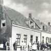 G0411 <br /> De graanmaalderij van Cornelis van Niekerk aan de Hoofdstraat. Het grote witte pand uiterst rechts is het (tijdelijke) zusterhuis tot 1898. Nu is hier bakker Ammerlaan-BroodGewoon.  <br /> Van Niekerk staat in de deuropening met een zwartzijden pet op. De mannen in het wit behoren waarschijnlijk tot het personeel. In 1898 stortte het gebouw in en op deze plaats is een woning met zadelmakerij voor J. v.d. Meer gebouwd. Van Niekerk verhuisde naar de hoek Oude Haven/Vaartkade. Foto vóór 1898.