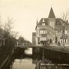 G0446 <br /> De Sassenheimervaart met de Klapbrug. Rechts het pand waar later Barend van Loo zijn sigarenwinkel zou vestigen. Daarnaast het huis van de fam. Juffermans en uiterst rechts de verbouw van drogisterij Melman (De Hoek). Links slagerij L. Persoon met de huisjes, die in 1930 zijn afgebroken. Foto: vóór 1930.