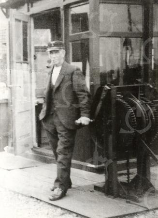 G0016 <br /> S.L.J. van der Kraan bij het bedieningsrad waarmee de bomen werden op- of neergelaten. Hij staat voor het wachthokje bij de spoorwegovergang Klinkenberg. Foto: 1932.