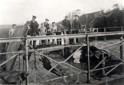 G0001 <br /> Een breuk in het wegdek van de Postbrug over de Haarlemmertrekvaart aan de Rijksstraatweg vlakbij de grens van Oegstgeest en Sassenheim. Op de achtergrond de boerderij Duivenvlugt van de fam. Bouwmeester. <br /> De derde man van links is vermoedelijk de kantonnier van Rijkswaterstaat, dhr. Van Kesteren. Foto: 1910.