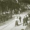 G1830 <br /> Historisch-allegorische optocht tijdens het onafhankelijkheidsfeest in 1913. We zien hier het laatste deel van groep 3 van de stoet met links een karos, getrokken door vier paarden en bereden door twee jockeys en met een lakei achterop. In de karos o.m. mej. A.H.J.S. Wüstenhoff als Hare Keizerlijke Majesteit Maria Louise van Oostenrijk, Napoleons tweede gemalin. De foto is genomen op de Hoofdstraat ter hoogte van de Pancratiuskerk, waar nu de Parklaan begint. Aan de overzijde van de weg achter de bomen zien we het ijzeren toegangshek naar villa Casa Reale. <br /> Foto: 18 september 1913.