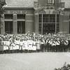 G1820 <br /> Het eeuwfeest 1813-1913, het onafhankelijkheidsfeest. Kinderen van de School met den Bijbel staan hier 's morgens op 18 september 1913 gereed voor de optocht door het dorp naar het feestterrein op de Overplaats. De jongens zijn gescheiden van de meisjes. Allen dragen een oranjesjerp; de meisjes als ceintuur om hun middel, de jongens over hun schouder. Foto: 1913.