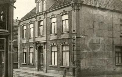 G0408 <br /> Het huis van de fam. Vlasveld op de hoek Hoofdstraat/Kerklaan, afgebroken in 1933. In vroeger tijd hingen tussen de palen op de stoep kettingen. Het huis daarnaast is van de fam. Bruijnen. Links op de voorgrond een hoekje van hotel café-restaurant 't Bruine Paard. Foto: vóór 1933.