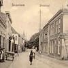G0414 <br /> Links het pand van J.v.d. Meer, daarna de korenmaalderij, later wijnhandel. Dan volgt boekhandel J.W. de Gruijter en het witte huis, dat tot 1899 als zusterhuis en school gebruikt werd. Later kwam bakker Hooijmans in het pand. Rechts een deel van het woonhuis van Bruijnen. Via de poort was de smederij te bereiken. Het volgende pand was jarenlang de winkel van C. Jamin. Daarna het huis van T. Vos, de kolenhandel. Foto: 1910.