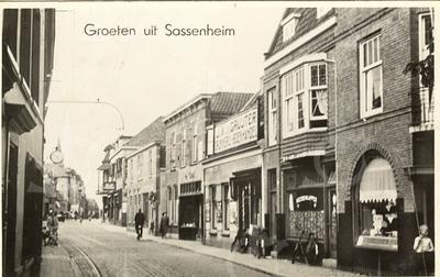 G0422 <br /> Uiterst links de zaak van G. Bemelman, schilder en klompenhandel. Verder de klok boven de winkel van C. Jamin. Rechts de bakkerszaak van Hooijmans, dan de kapperszaak van Fok van Dijk. En verder de winkels van De Gruijter, van Niekerk, Van der Meer en hotel café-restaurant 't Bruine Paard. Foto: 1943.