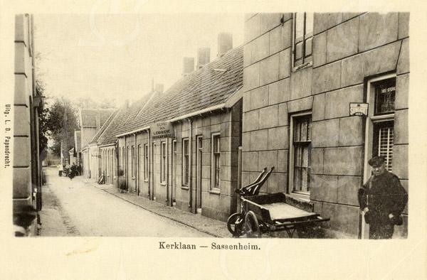 G0409<br /> Kerklaan. Rechts op de voorgrond het woonhuis en winkel van Künemann (later C.J. Verlint). De man rechts is de vader van Künemann. Verderop de huisjes van de diaconie (Ned.-herv.). Hier hebben o.a. Ph. Bakker (wagenmaker) en K. den Boer (koster van de Ned.-herv. kerk) gewoond. De laatste woonde op nr. 2, het eerste huisje rechts, naast de poort. Later woonde hier Gerrit de Bruijn samen met zijn zus mevr. C. Duijm-de Bruijn. Het hoge gebouw op de achtergrond is de wagenmakerij van Ph. Bakker, gebouwd in 1895.